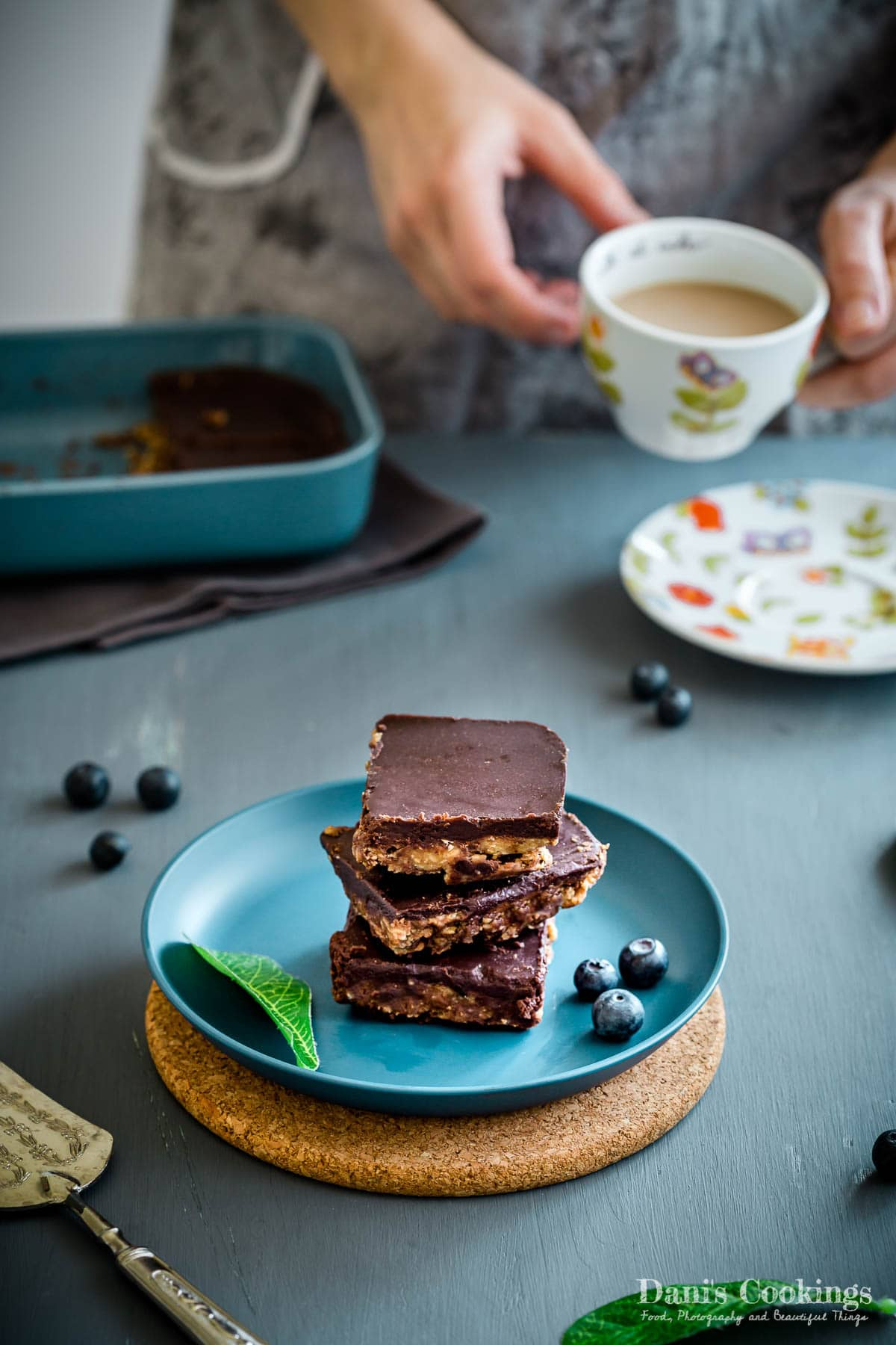 cookie dough bars on a plate with a woman with coffee on the back