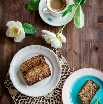 zucchini bread slices in two plates with coffee and flowers aside