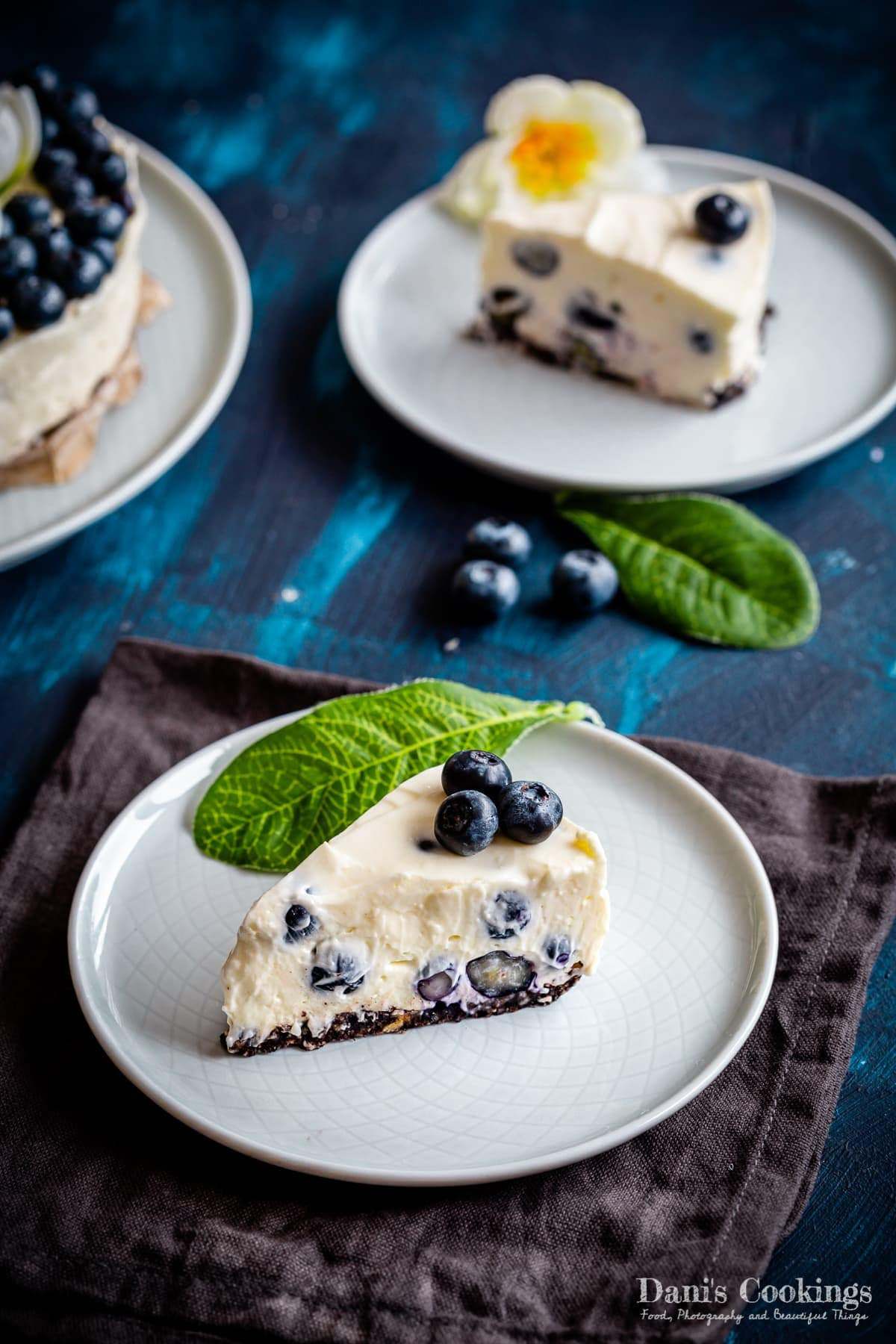 a slice of blueberry cheesecake with another one aside