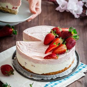 a strawberry ice cream cake with a slice cut out