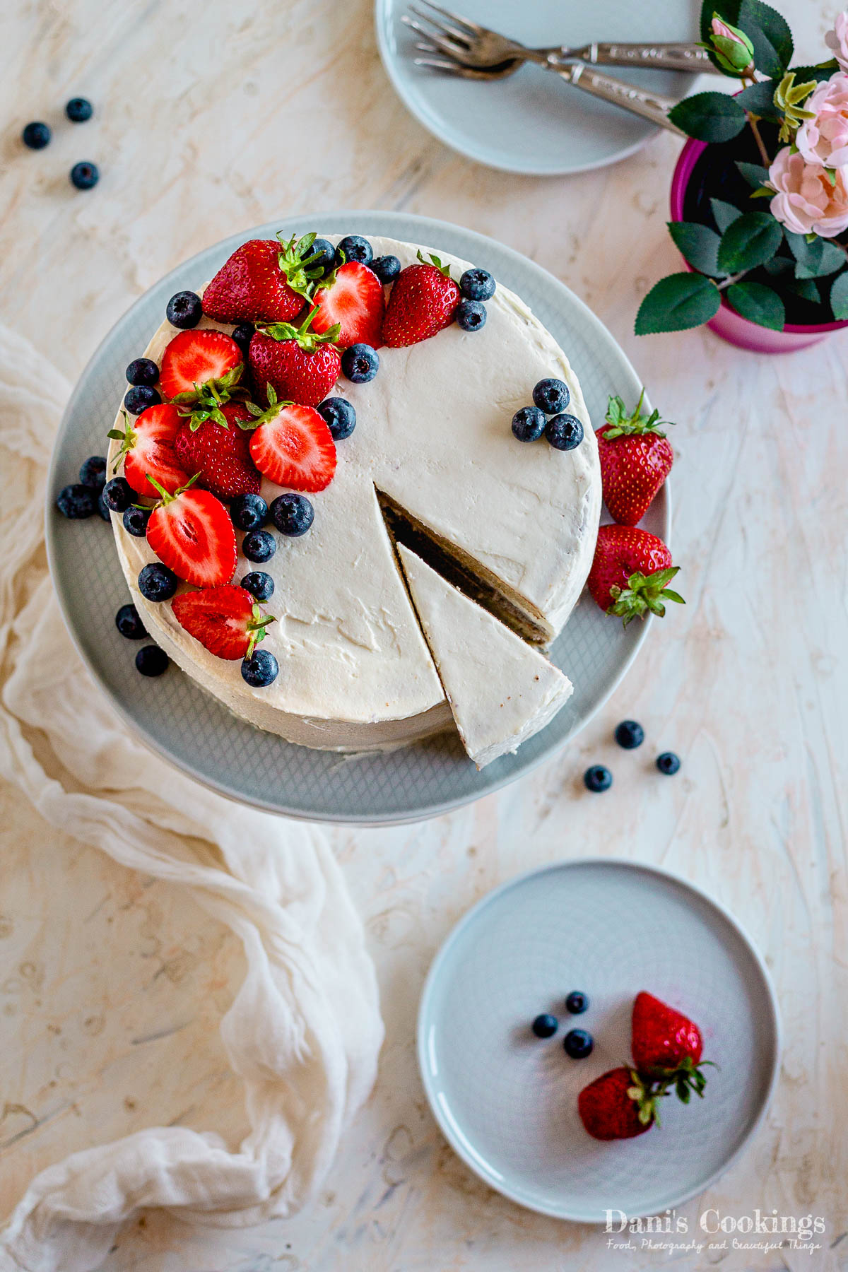 white birthday cake with strawberries and blueberries - flat lay