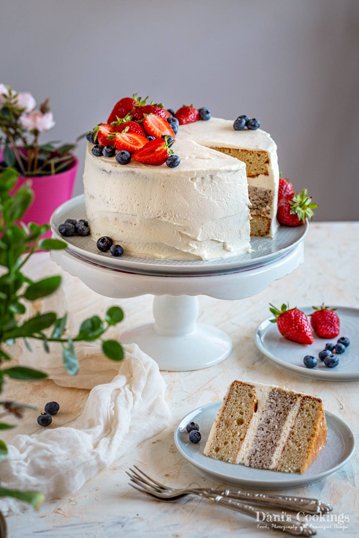 white layer cake with strawberries and blueberries, sliced