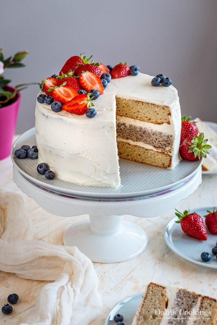 sliced birthday layer cake with strawberries and blueberries