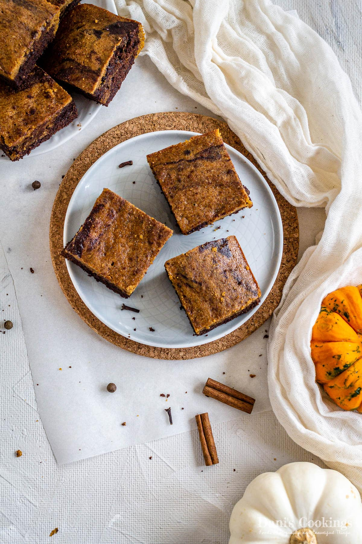 a flat lay of three brownies on a plate with more brownies and pumpkins aside