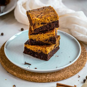 three stacked pumpkin brownies on a plate