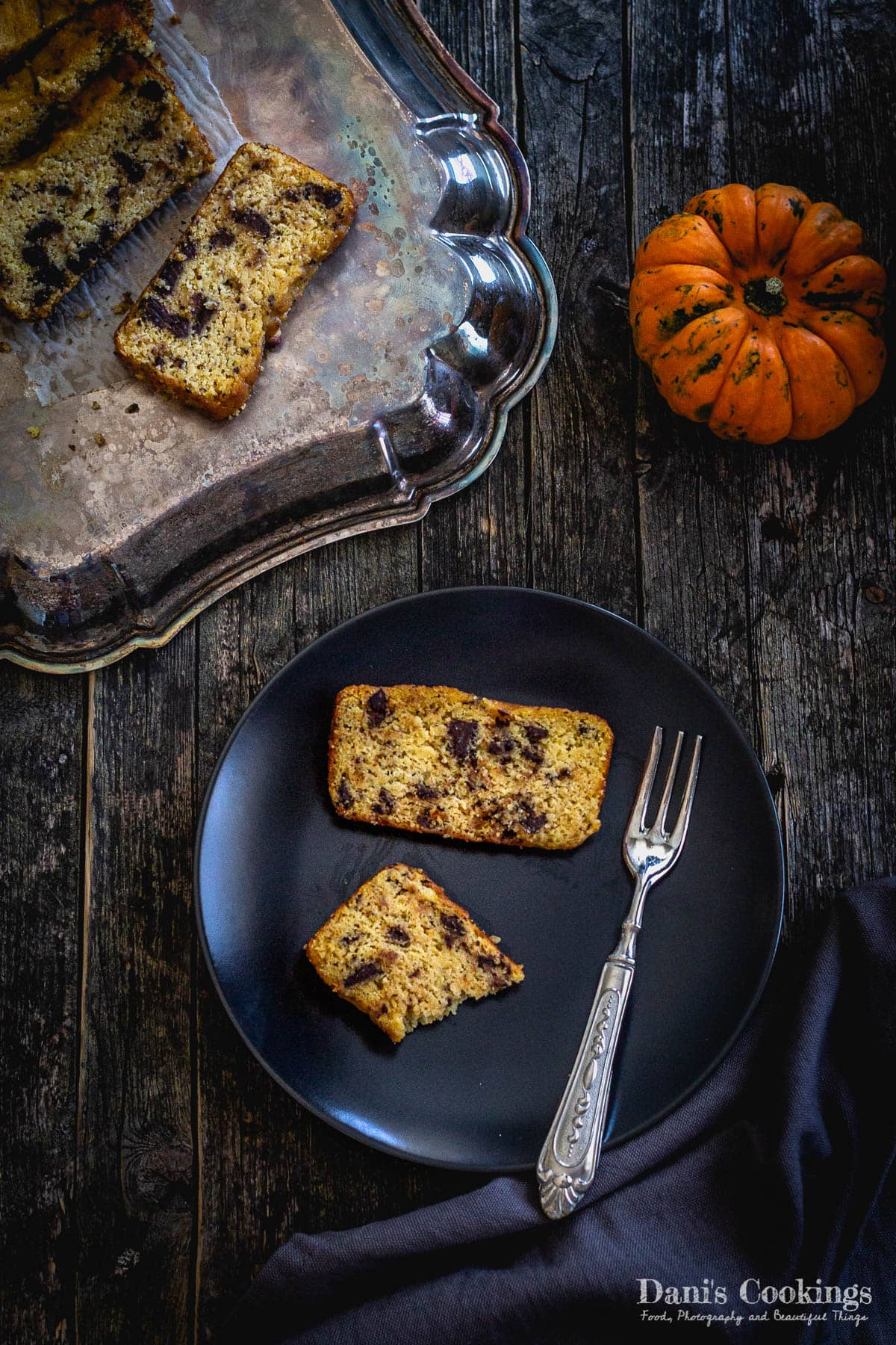 pumpkin bread slices on a plate with pumpkin aside