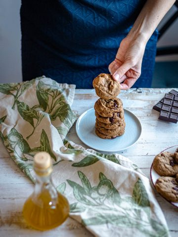 a woman piling cookies on a plate