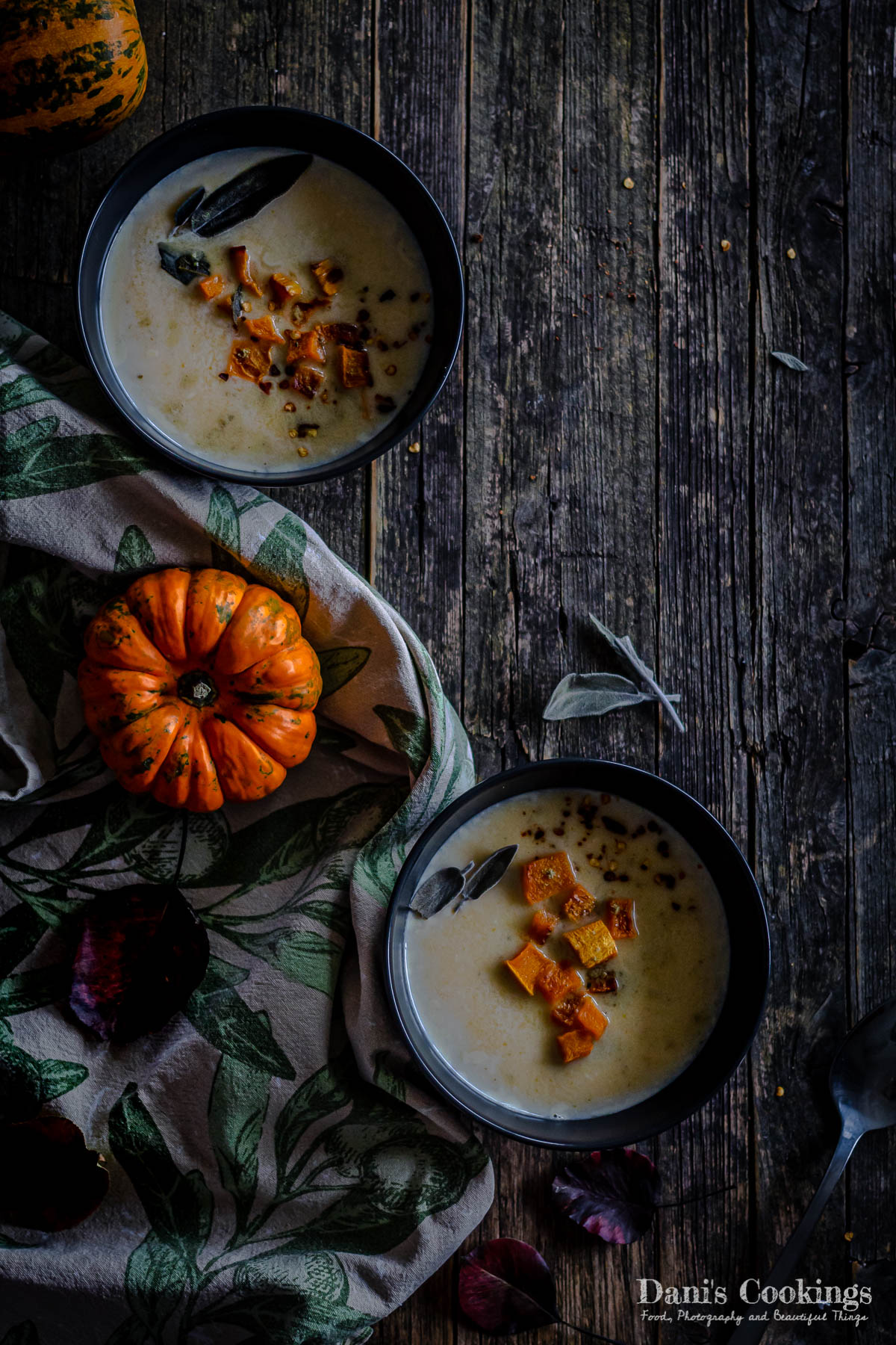 two bowls of pumpkin soup on a wooden background, flat lay