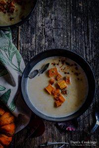 a bowl of pumpkin soup with pumpkin cubes flat lay