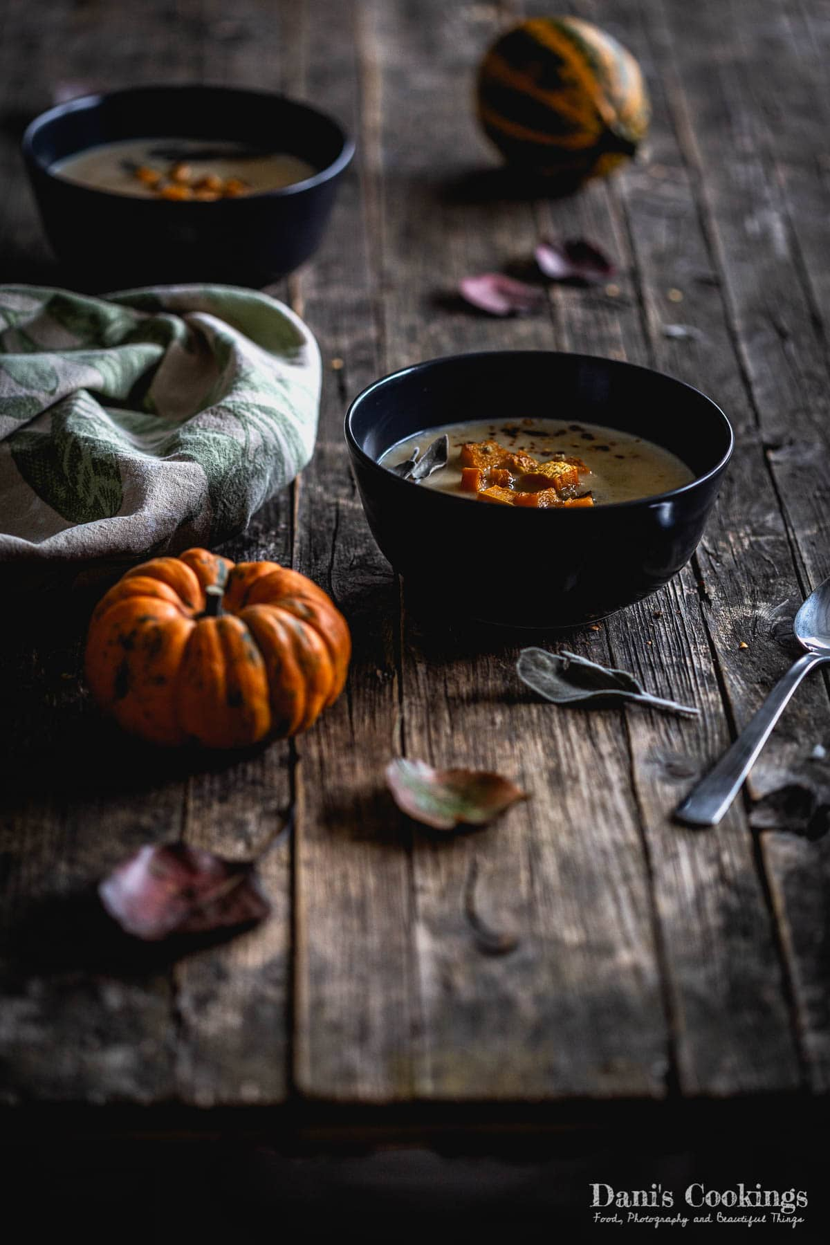 two bowls of pumpkin soup on a table with pumpkin aside