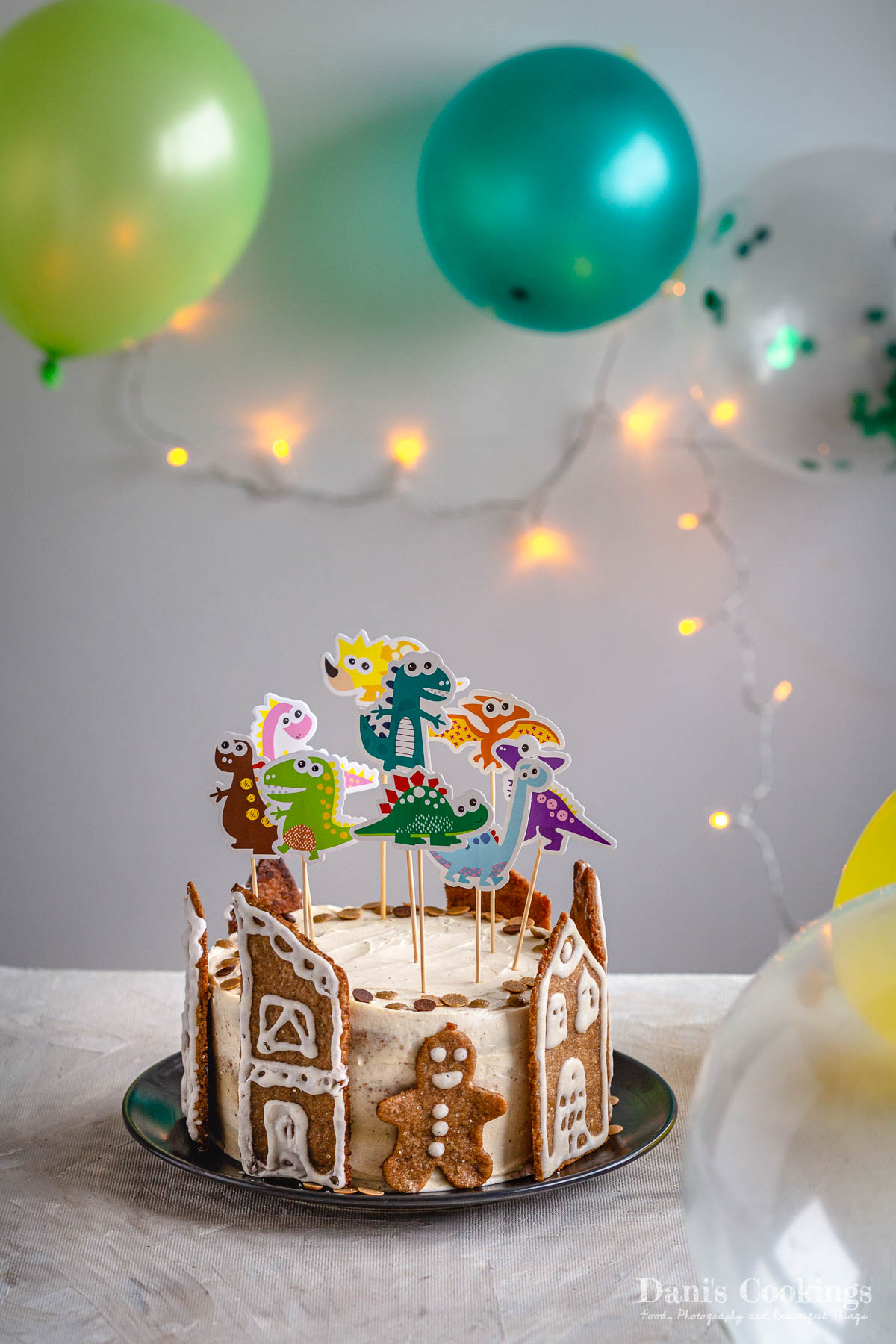 birthday pinata cake with dinosaur toppers and balloons aside