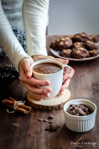 a woman holding a cup of hot chocolate with cookies aside