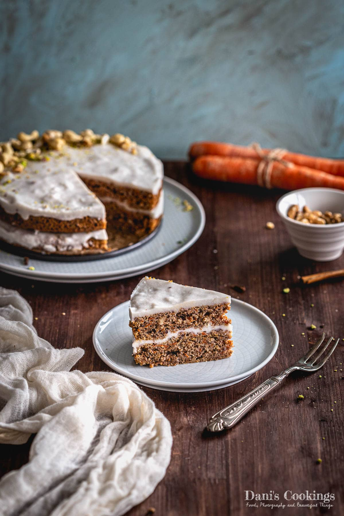 a sliced carrot cake with nuts and carrots aside