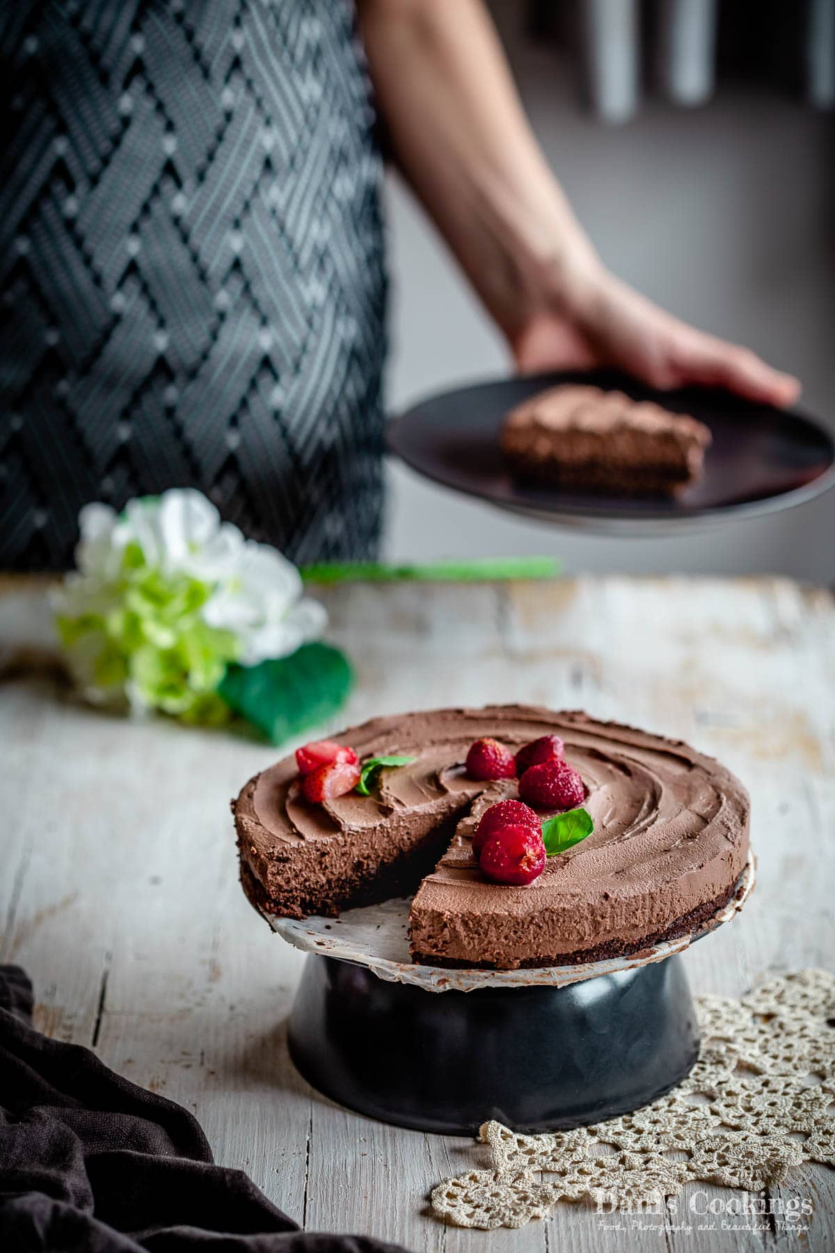 a woman holding a slice of cake behind the chocolate mousse cake