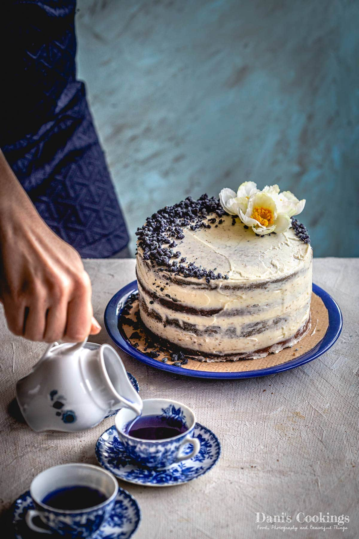 a woman pouring blue tea next to a layer cake