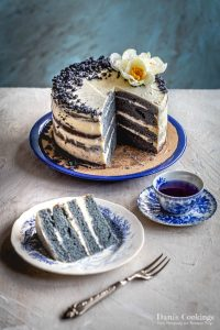 a cut cake with a blue slice and tea aside