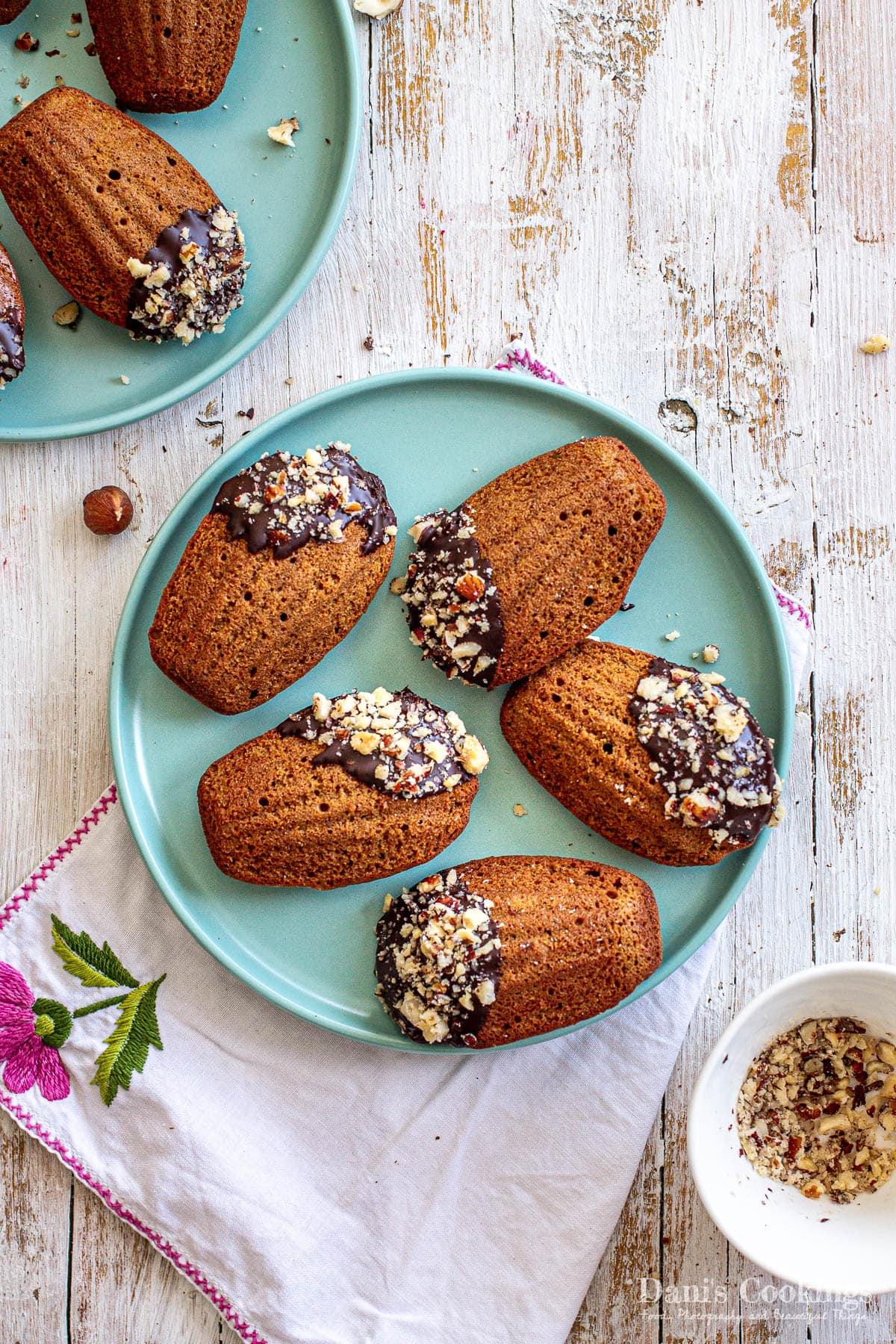 two plates with chocolate coated hazelnut madeleines on a wooden background