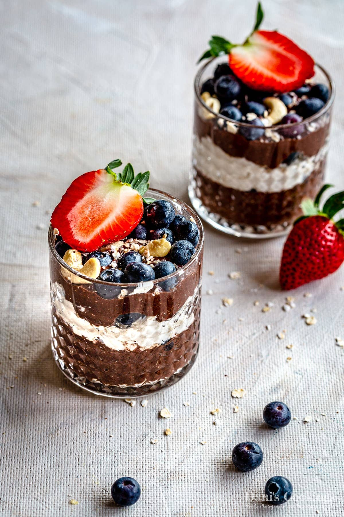 two glasses with chocolate trifles with berries and oats