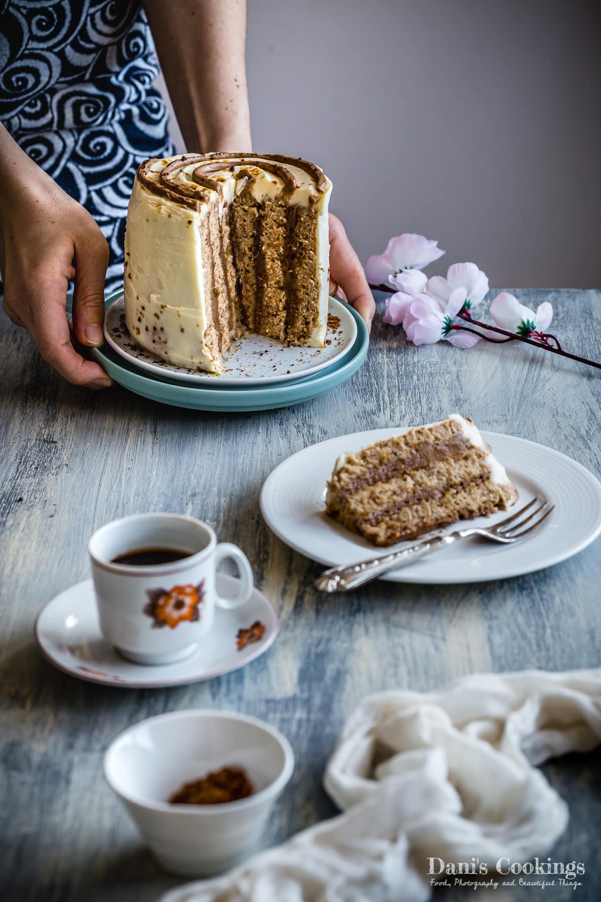 a woman holding a sliced vertical cake next to coffee and a slice