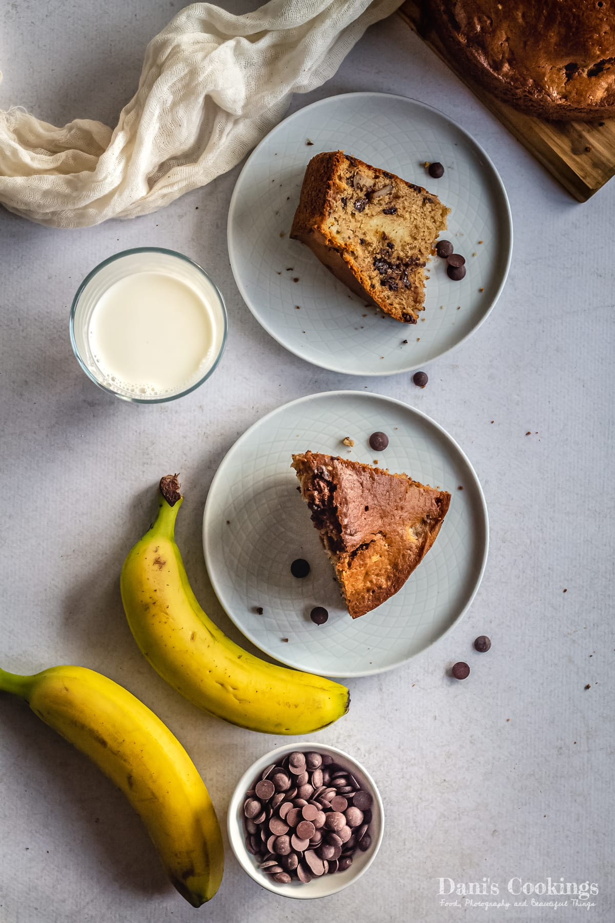 two slices of banana bread with milk and chocolate chips and bananas
