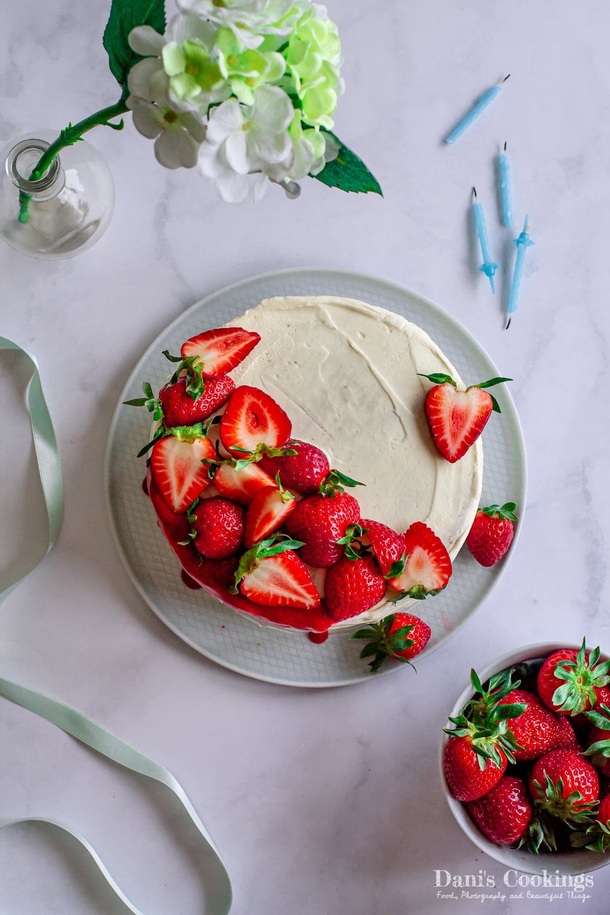 a flat lay of a cake with strawberries with birthday candles aside