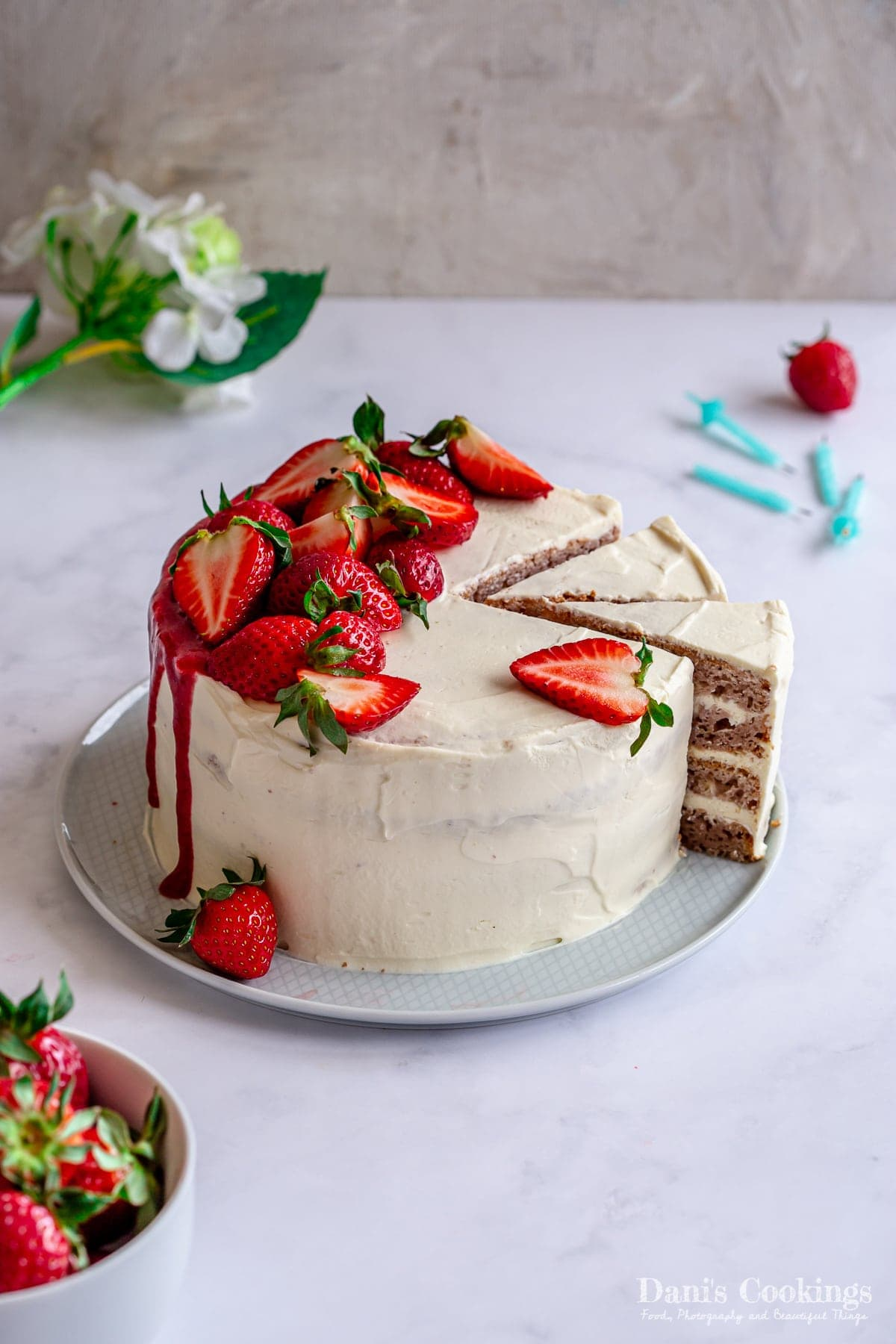 a layer cake with strawberries on top and aside