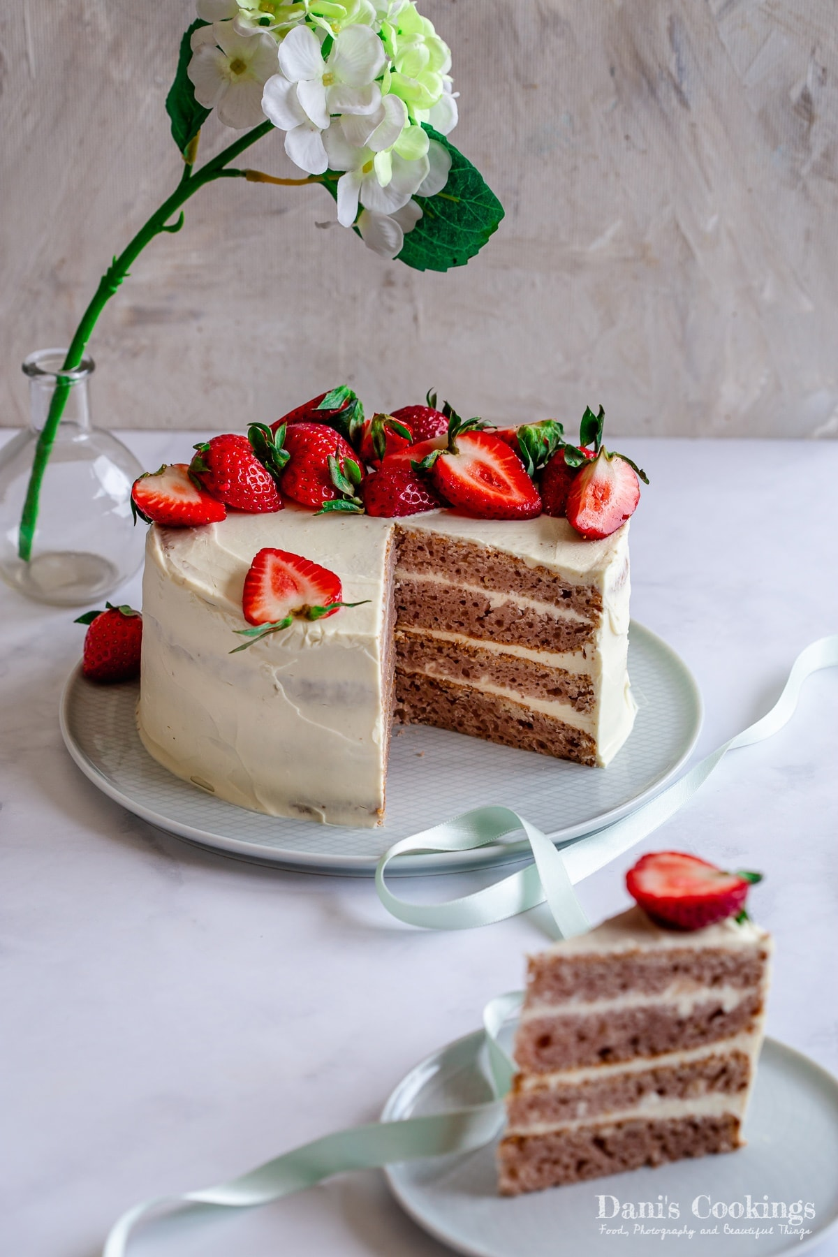 a sliced layer cake with strawberries and a piece of it aside