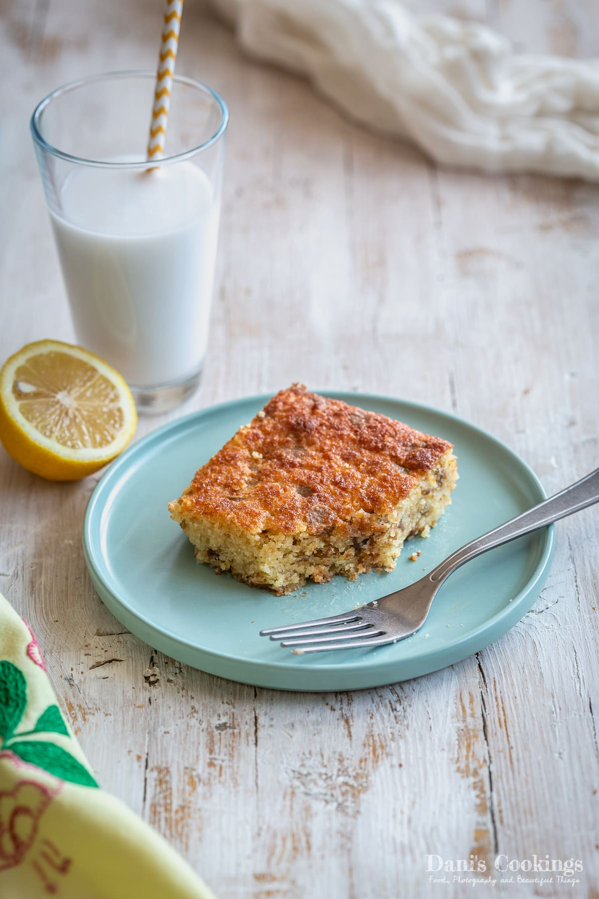 a blondie served on a plate with milk and lemon aside