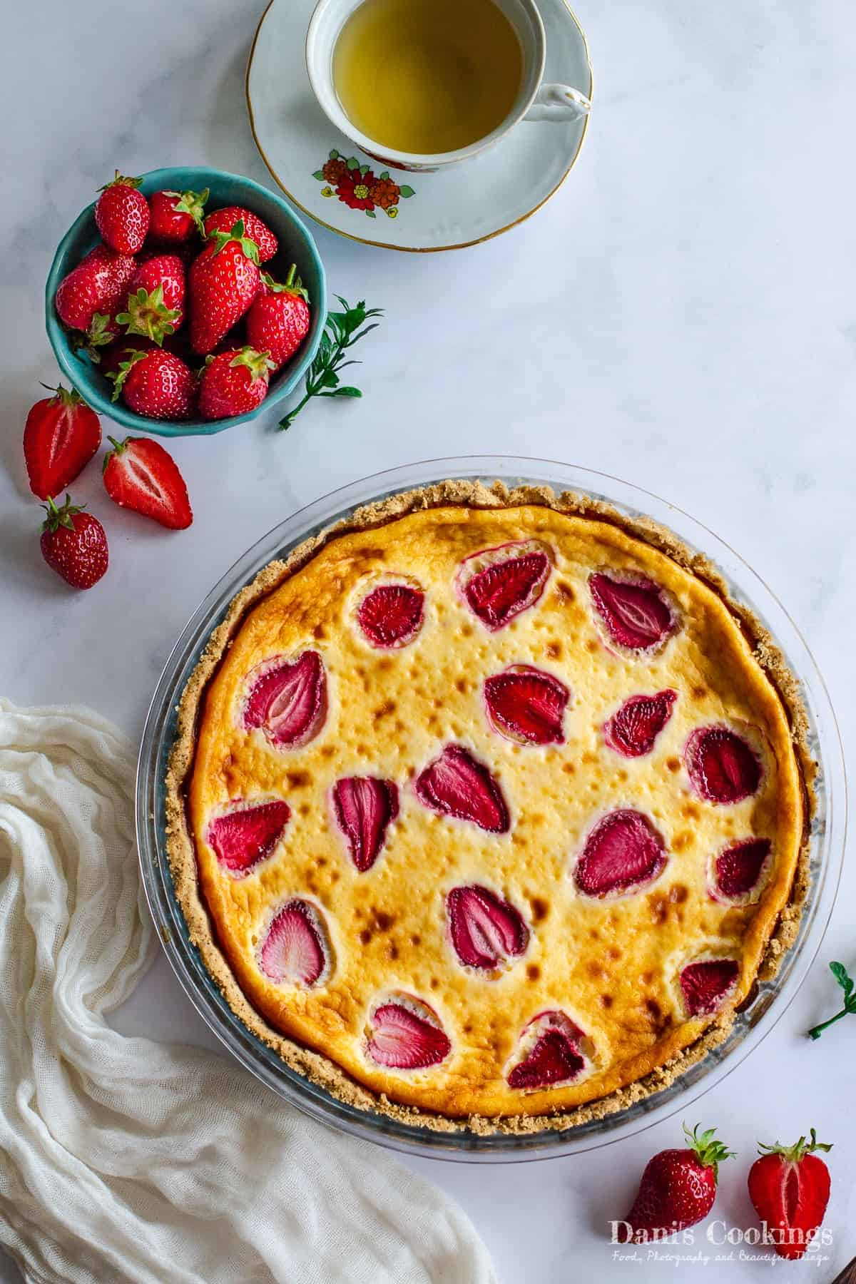 a baked tart with strawberries on a marble texture with tea and fresh strawberries aside