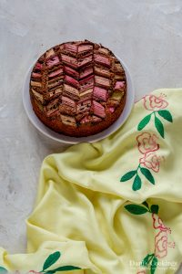 a rhubarb cake on a plate with yellow cloth aside