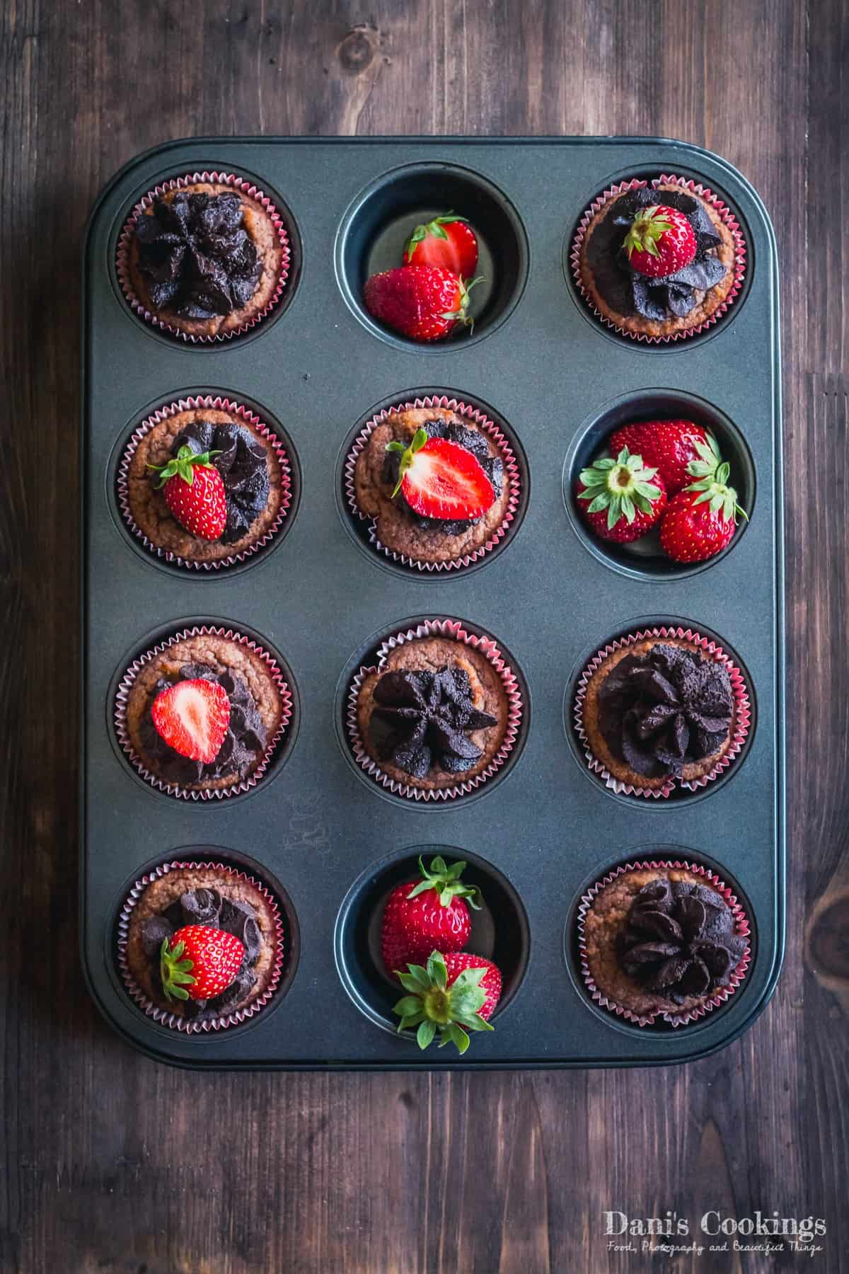 cupcakes with strawberries and chocolate frosting in a muffin tin