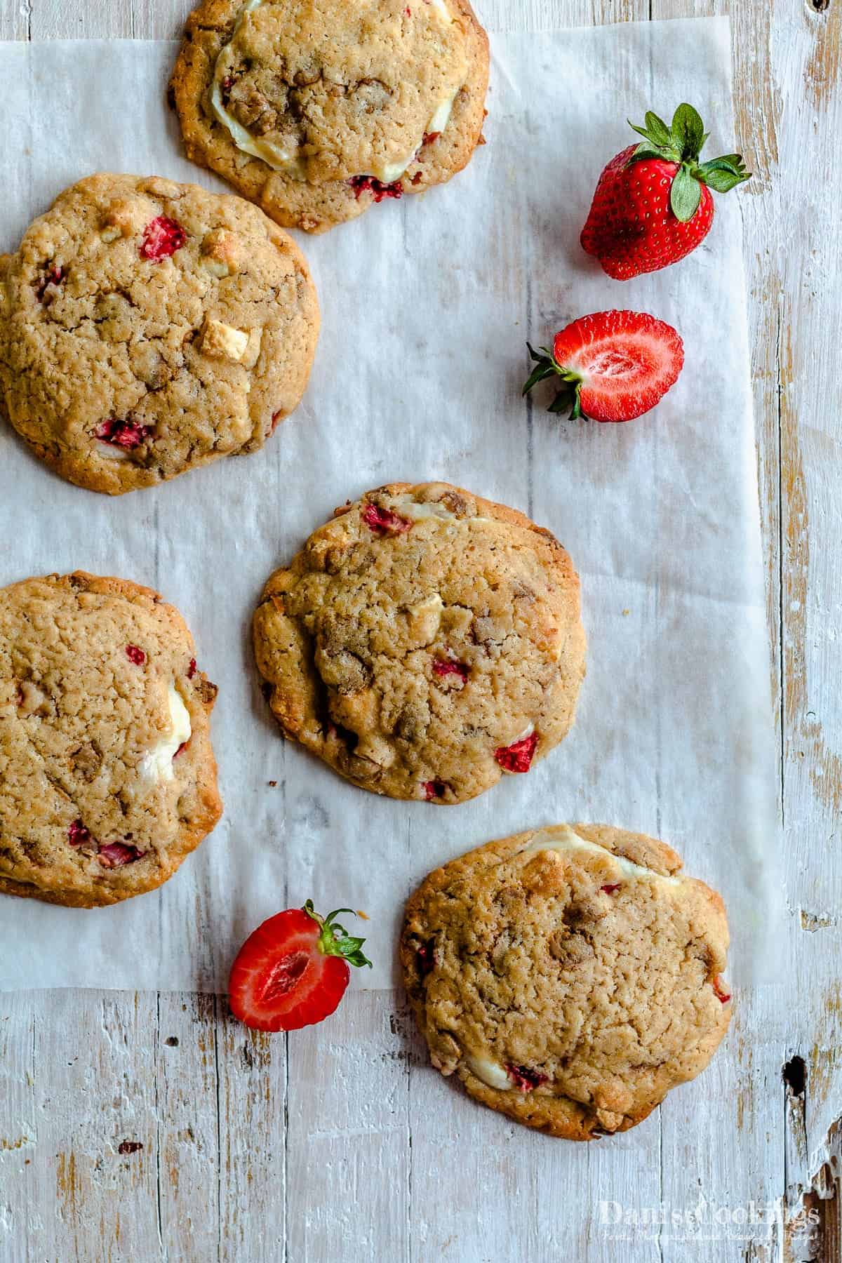 a flat lay image of cookies with strawberries aside
