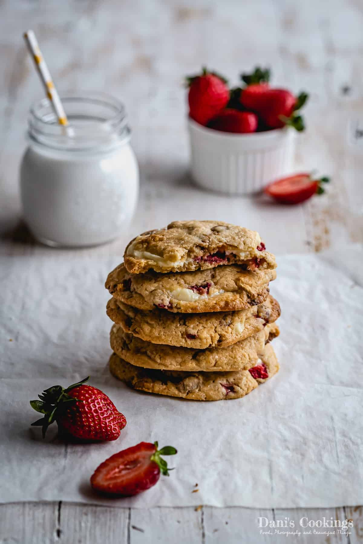 four and a half stacked cookies with milk and strawberries aside