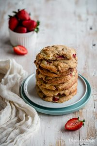 stacked cookies on plates with strawberries aside