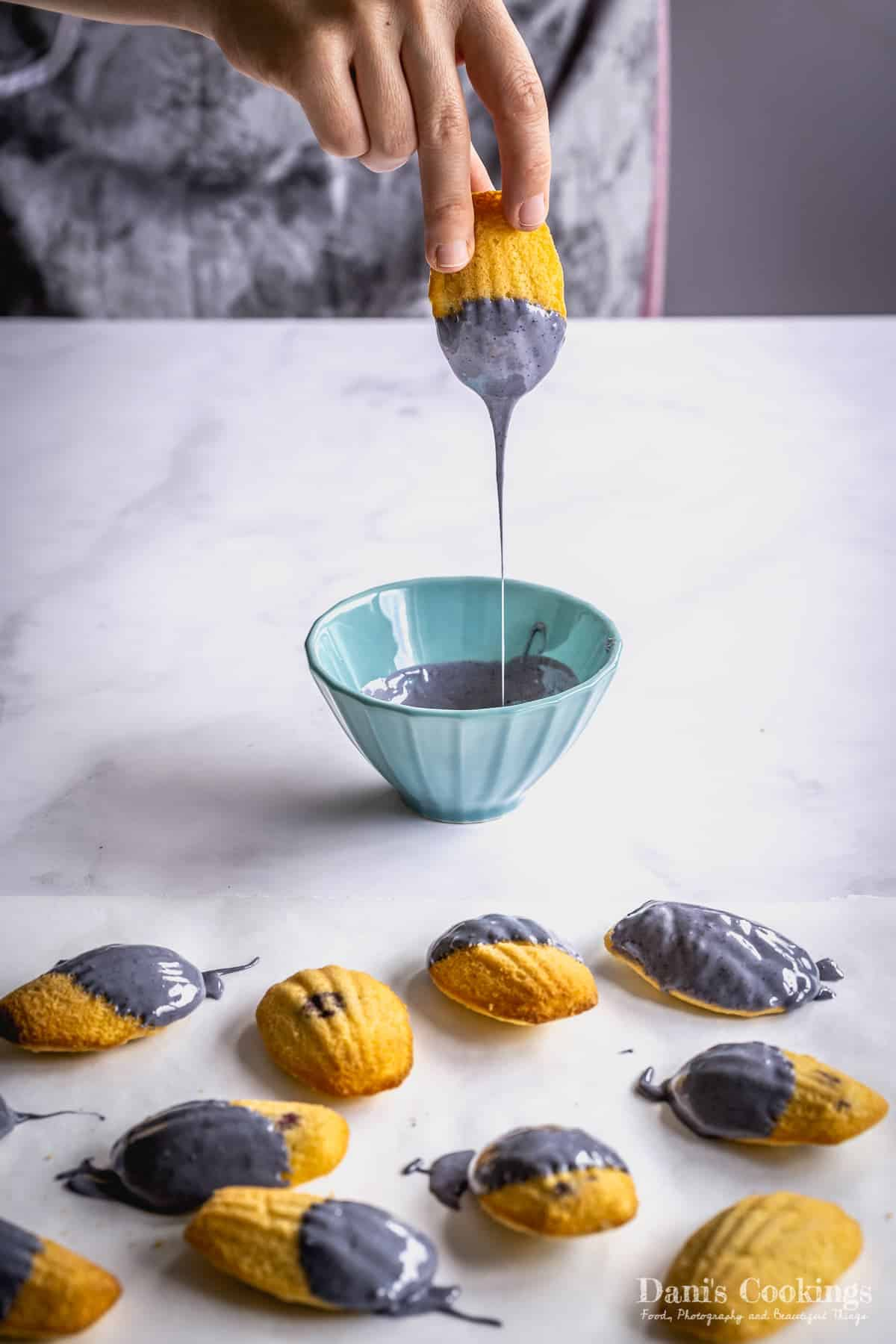 a woman dipping madeleines in blue chocolate