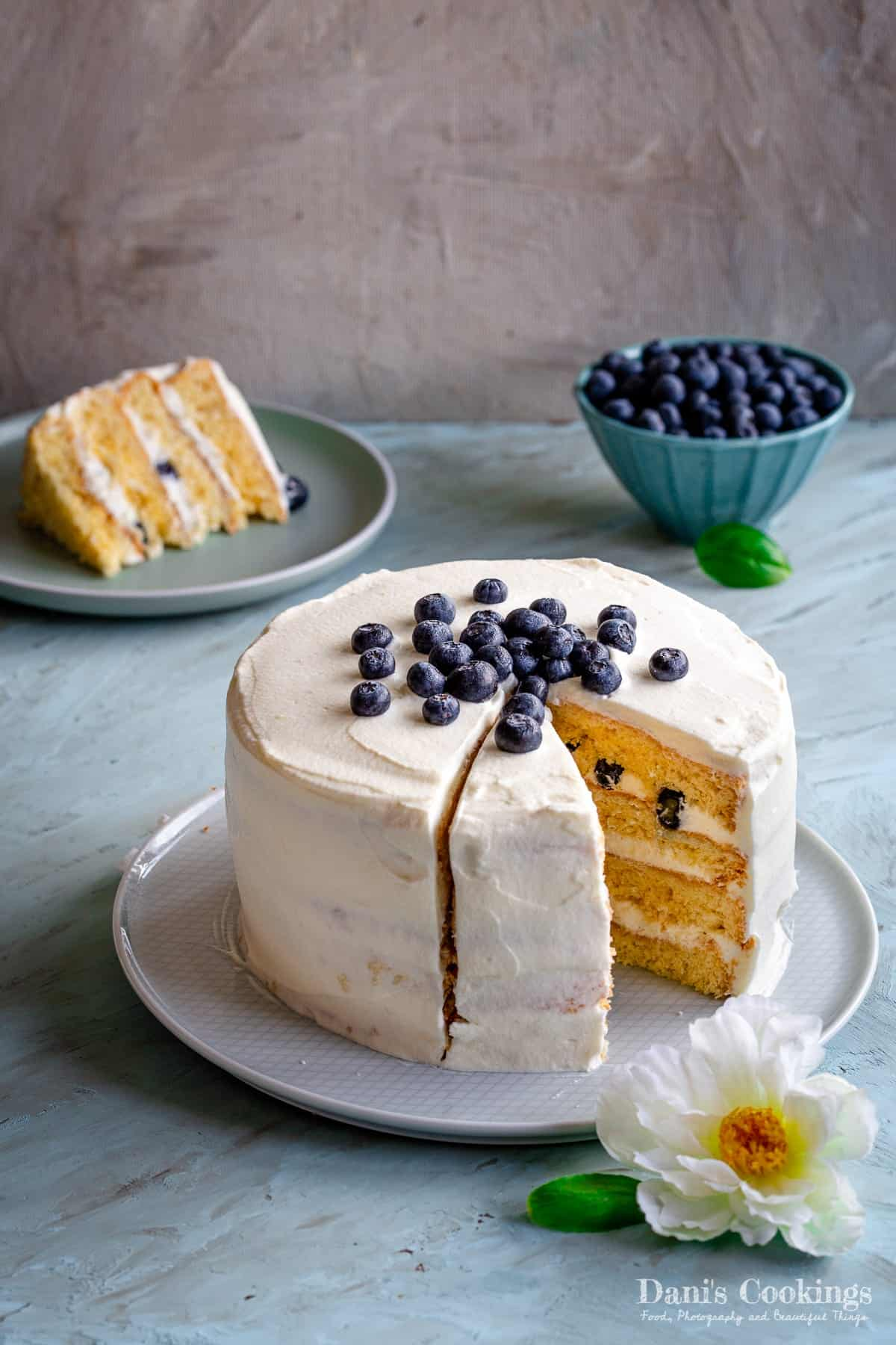 a layer cake with white frosting and blueberries aside and on top