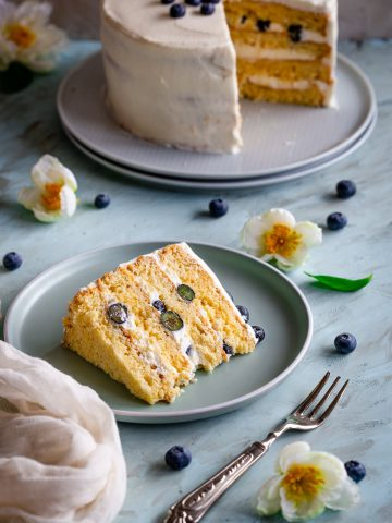a cake slice with blueberries and the whole cake behind