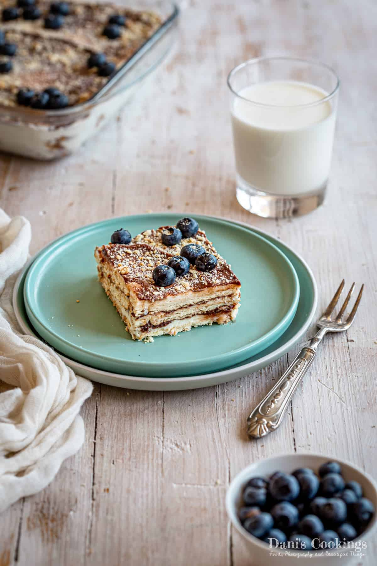 a slice of cake with blueberries and milk aside