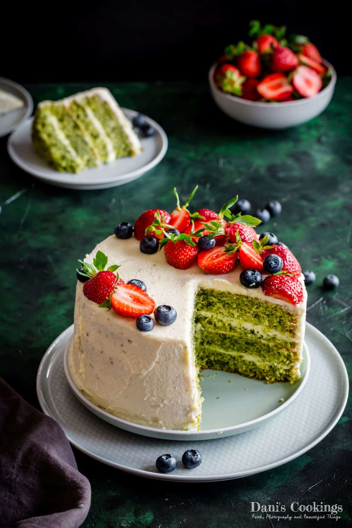 a cake with green layers and white frosting and berries, cut