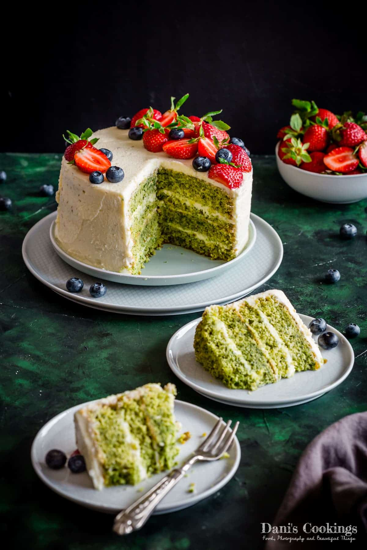 a green cake with white frosting cut with pieces aside