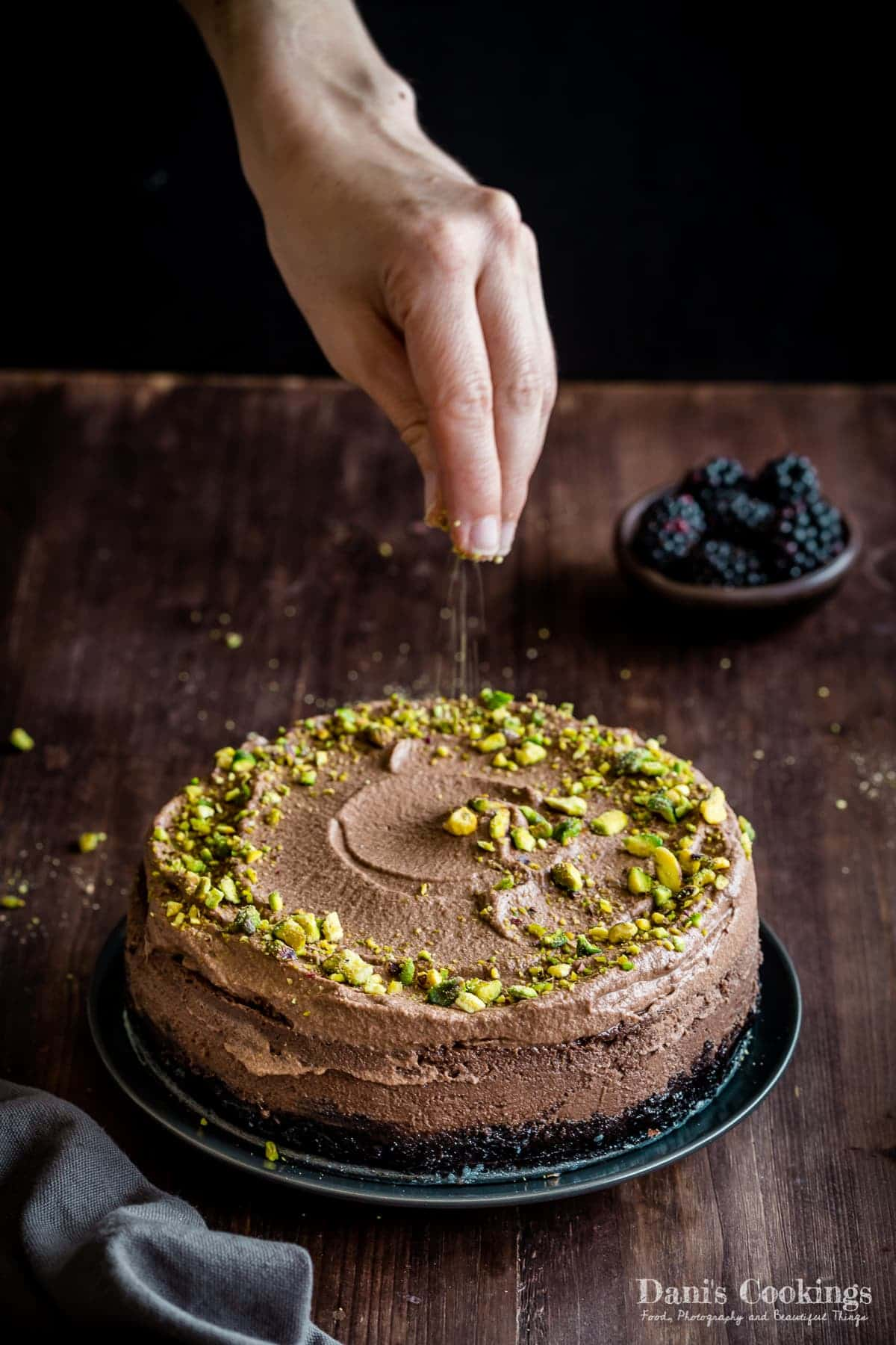 a woman sprinkling a chocolate cheesecake with pistachio