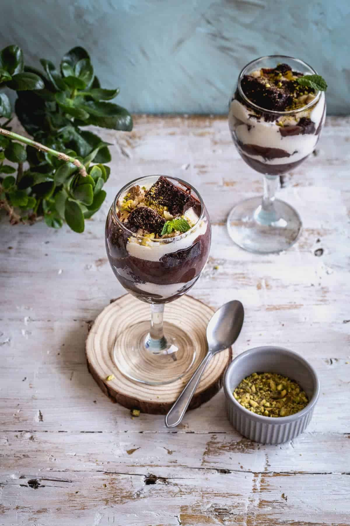 two trifles next to a plant with a spoon aside one