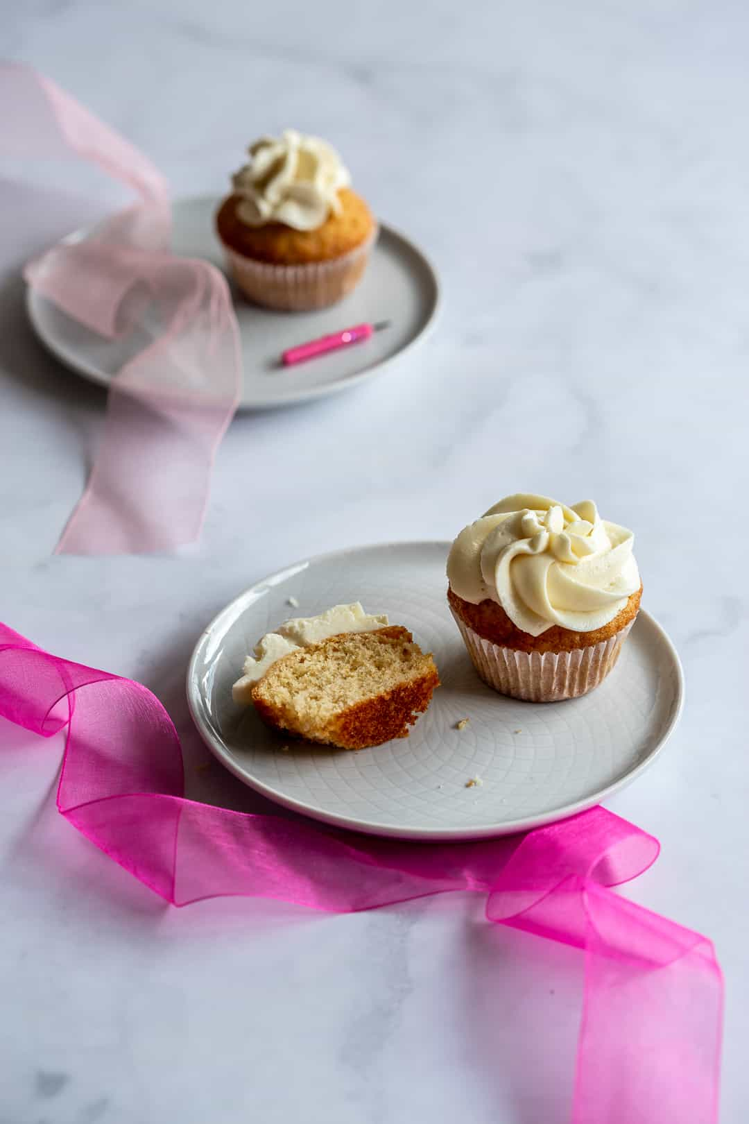 cupcakes on two plates with a candle on one