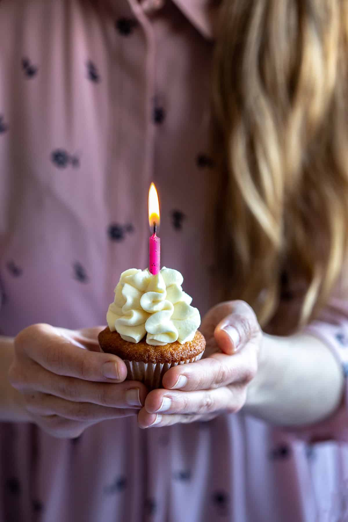 a woman holding a cupcake with a candle
