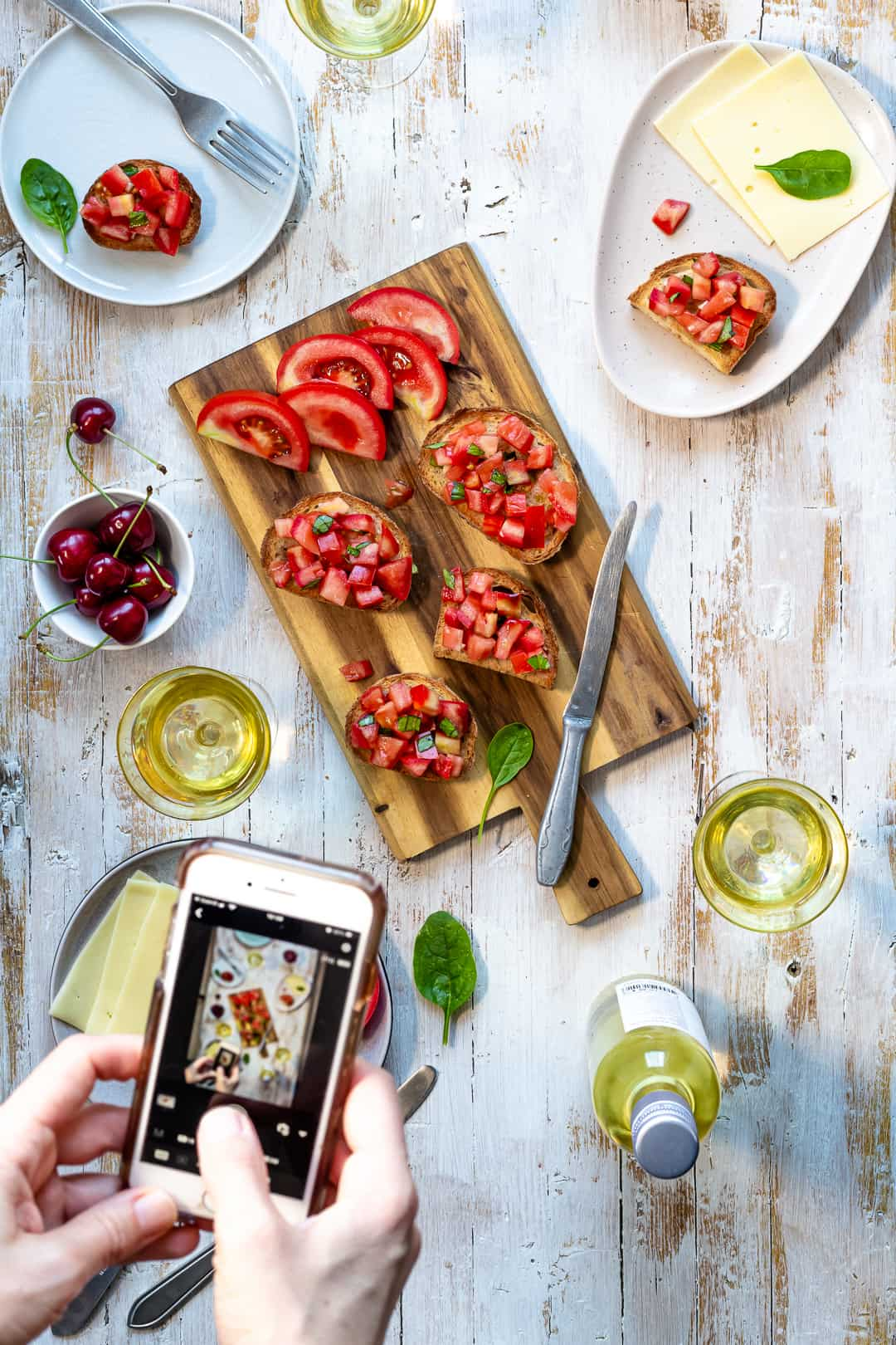 a woman taking mobile photo of a scene with bruschetta