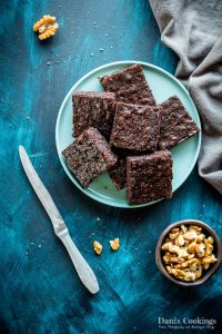 brownies on a plate with walnuts and napkin aside