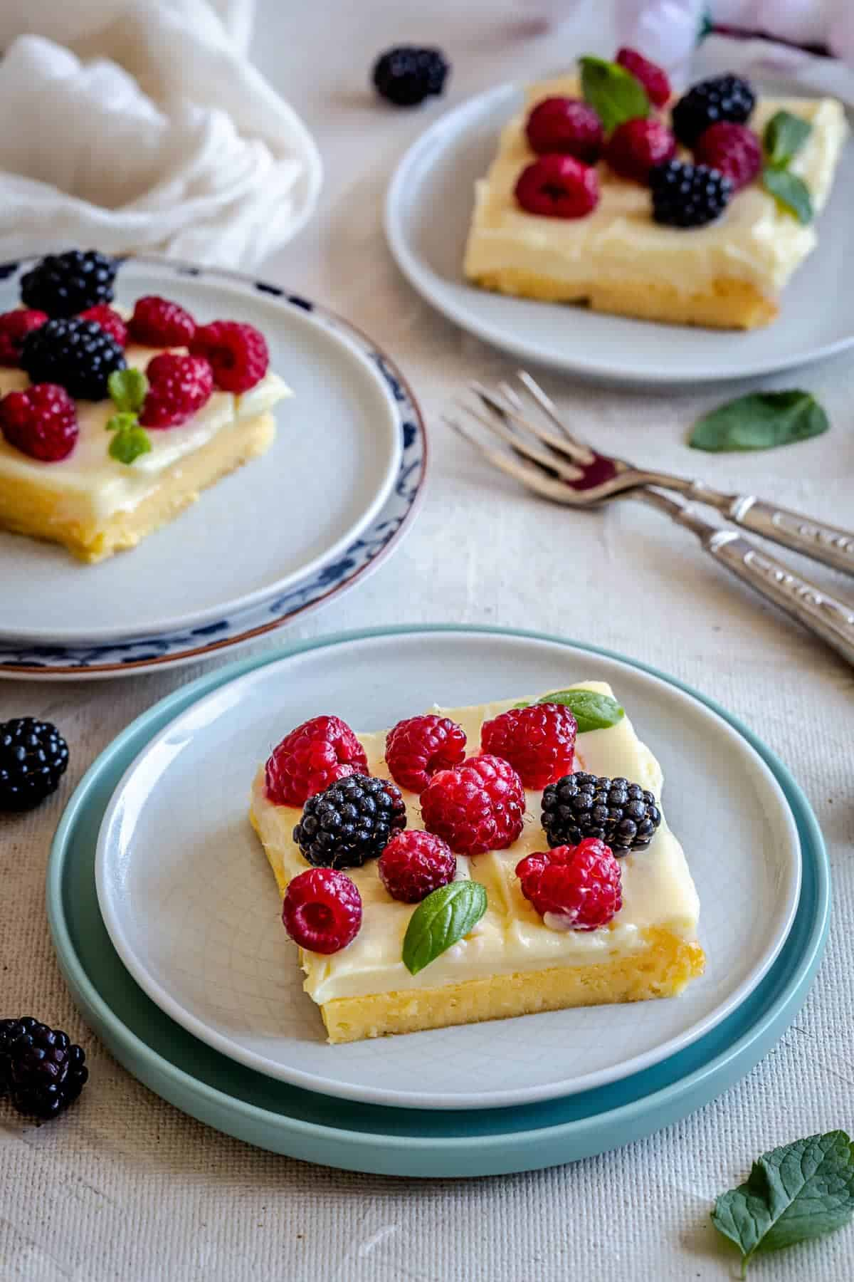 yellow bars with frosting and berries on top served in plates