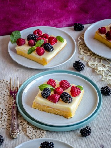 creamy bars with berries on top served in plates
