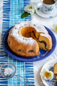 a marble bundt cake with one slice taken off and icing sugar aside