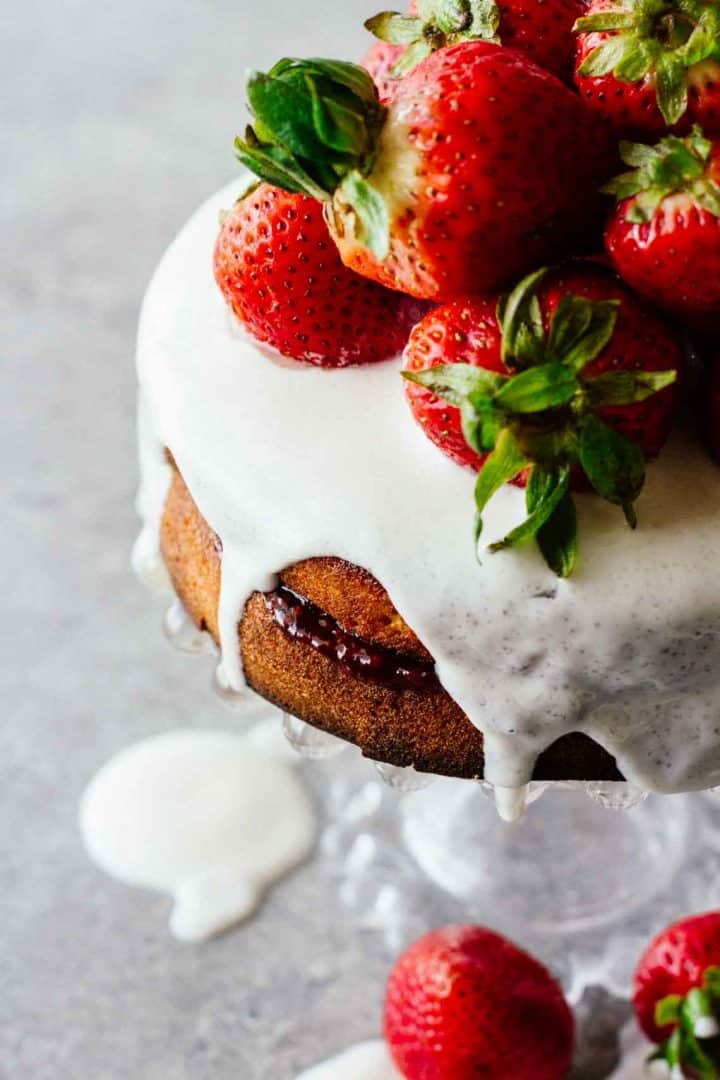 a cake with strawberries and white glaze